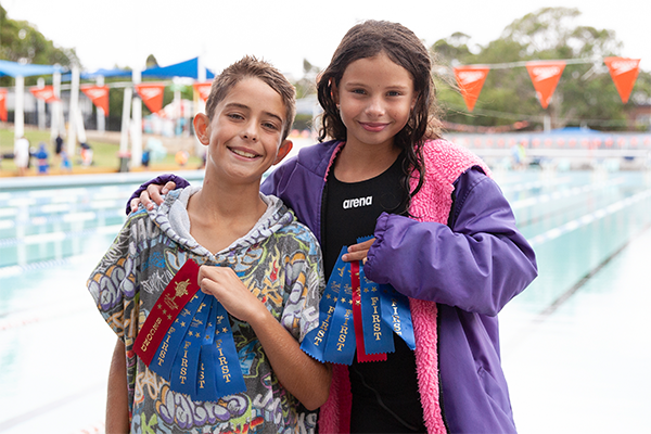 Sibling swimmers with ribbons from the swimming carnival